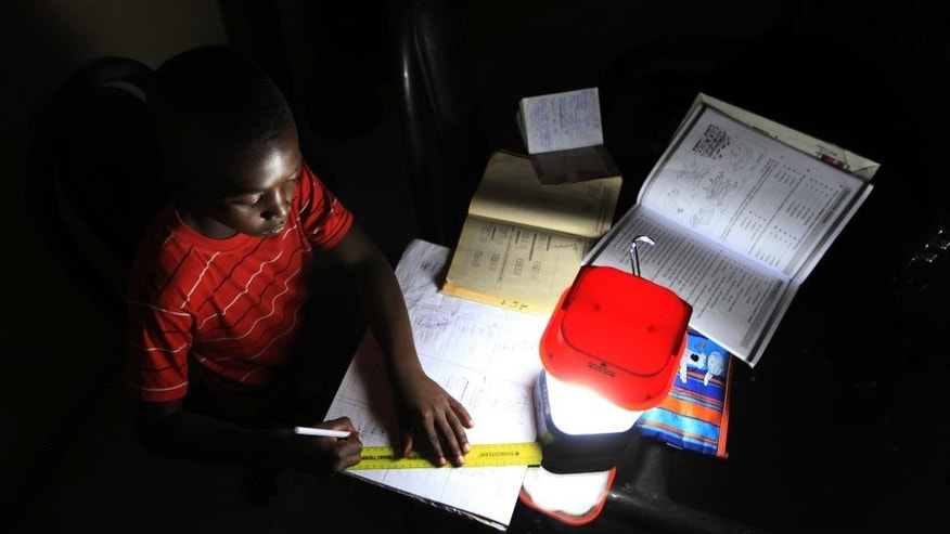 In this photo taken Wednesday Sept. 2015, a student does his homework using a solar lantern in Harare, Zimbabwe. The normal rains did not fall, which caused water levels to drop in dams that produce electricity, so local people and businesses across Zimbabwe and Zambia are suffering power black-outs for up to 48-hours at a time.  Some traditional chiefs blame an angry river god, but the government blames the lack of rain, and work to expand the Kariba power station will not be complete for at least three years, said Partson Mbiriri, permanent secretary in Zimbabwe's ministry of energy and power development. (AP Photo/Tsvangirayi Mukwazhi)