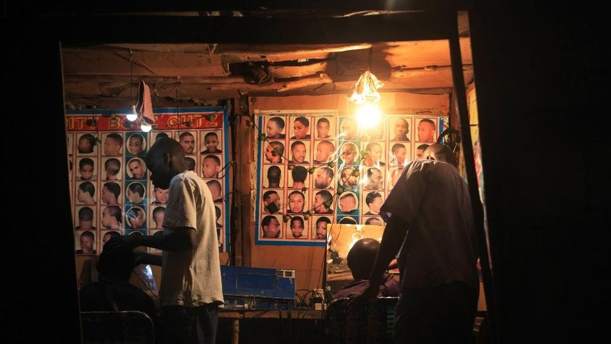 In this photo taken Wednesday Sept. 2015, a generator powers a makeshift barber shop in Harare, Zimbabwe.  The normal rains did not fall, which caused water levels to drop in dams that produce electricity, so local people and businesses across Zimbabwe and Zambia are suffering power black-outs for up to 48-hours at a time.  Some traditional chiefs blame an angry river god, but the government blames the lack of rain, and work to expand the Kariba power station will not be complete for at least three years, said Partson Mbiriri, permanent secretary in Zimbabwe's ministry of energy and power development.(AP Photo/Tsvangirayi Mukwazhi)