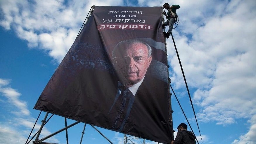 "Israeli workers hang up a billboard with a portrait of late Israeli Prime Minister Yitzhak Rabin, ahead of a memorial rally for the 20th anniversary of his assassination at Rabin square in Tel Aviv, Israel, Friday, Oct. 30, 2015. Hebrew on the billboard reads ""Remembering the murder, fighting for democracy."" Twenty years after Yitzhak Rabin was gunned down by a Jewish extremist opposed to his negotiations with the Palestinians, Israel is more divided than ever over Mideast peacemaking _ and the people who opposed the assassinated premier with vitriol, led by Benjamin Netanyahu, now have a firm grip on power. (AP Photo/Oded Balilty)"