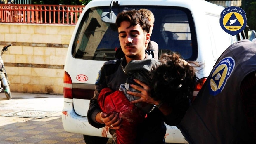 This photo provided by the Syrian anti-government activist group Syrian Civil Defense, shows a paramedic holding a child after witnesses said a market was hit by Syrian government forces in Douma, Syria, Friday, Oct. 30, 2015. (Syrian Civil Defense via AP)