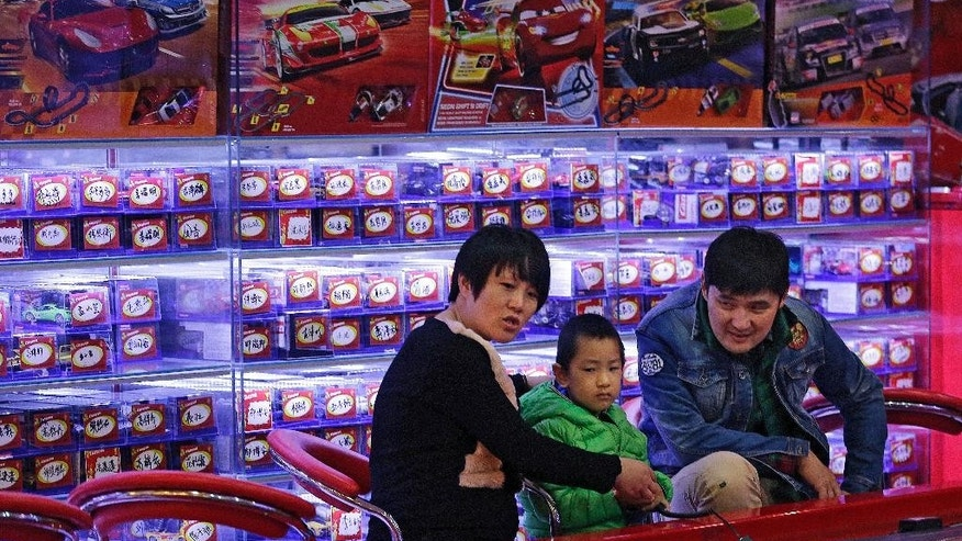 Parents and their child play with remote-controlled toy cars at a shopping mall in Beijing, Friday, Oct. 30, 2015. China's decision to abolish its one-child policy is a boon to couples and to sellers of goods from formula to diapers to toys. And it might help defuse economic stresses caused by an aging population. (AP Photo/Andy Wong)