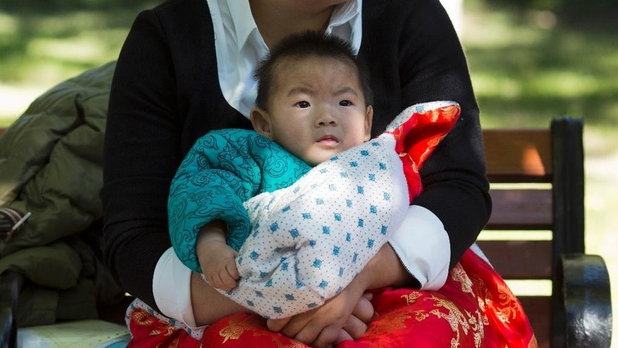 A child is wrapped up against the cold at a park in Beijing, China, Friday, Oct. 30, 2015.  Shares of companies making diapers, baby strollers and infant formula were getting a boost Friday from China's decision to scrap its decades-old one-child policy. (AP Photo/Ng Han Guan)