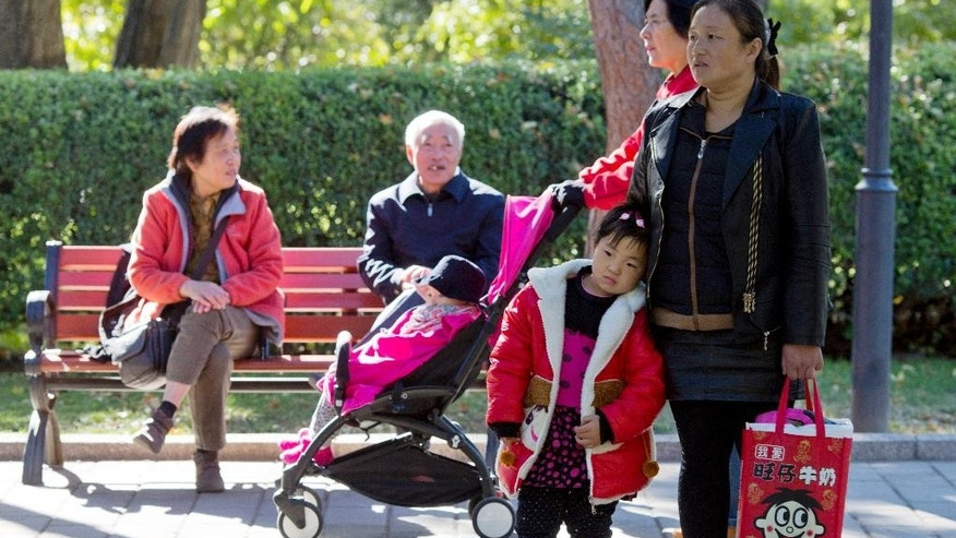 A child rests against a woman as another is pushed past in a stroller at a park in Beijing, China, Friday, Oct. 30, 2015.  Shares of companies making diapers, baby strollers and infant formula were getting a boost Friday from China's decision to scrap its decades-old one-child policy. (AP Photo/Ng Han Guan)