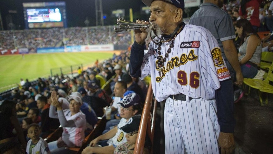 In this Oct. 27, 2015 photo, Jesus Lezama, a 96-year-old fan of the Leones de Caracas baseball team, blows a horn during a game against the Navegantes del Magallanes in Caracas, Venezuela. For years, Venezuela's raucous, boozy and affordable baseball games have provided respite from the growing gloom in the economically struggling country. Now, a more than 300 percent increase in ticket prices is putting a damper on the national pastime, with the season kicking off this month to half-empty stadiums and featuring players who say their per diems don't go far enough to buy lunch. (AP Photo/Ariana Cubillos)