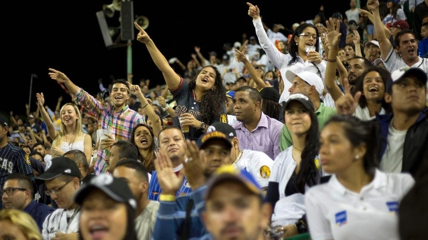 In this Oct. 27, 2015 photo, fans watch a game between the Leones de Caracas and the Navegantes del Magallanes in Caracas.  While most South Americans prefer soccer, Venezuela goes crazy for baseball. It's exported more players to the U.S. Major Leagues than any country aside from the Dominican Republic, including several who are playing for the Kansas City Royals in the World Series this week. (AP Photo/Ariana Cubillos)