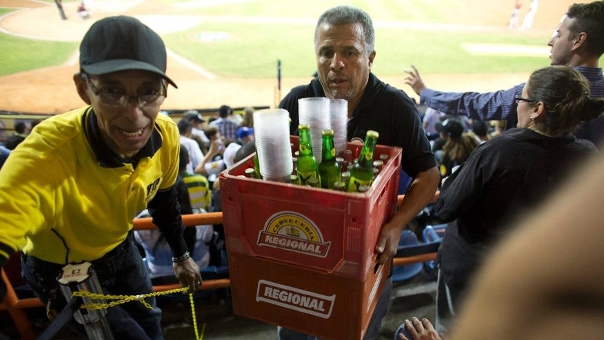 In this Oct. 27, 2015 photo, a vendor carries cases of beer during a baseball game between the Leones de Caracas and the Navegantes del Magallanes in Caracas, Venezuela. The fans are unhappy with the news that a bottle had jumped from 30 to 120 bolivars over the past year, and the most popular brands have gone missing altogether. (AP Photo/Ariana Cubillos)