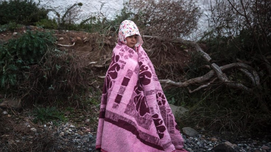 A boy tries to warm up on a beach with a blanket provided by volunteers shortly after arriving with around 125 people from the Turkish coast to the northeastern Greek island of Lesbos, Thursday, Oct. 29, 2015. Europe's largest refugee crisis since World War II is entering a perilous and uncharted phase, as the usual pattern of migrant season ending by autumn is overturned by intensifying fighting in Syria and overcrowding in refugee centers in Turkey and Lebanon.  (AP Photo/Santi Palacios)
