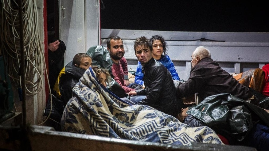 In this Wednesday, Oct. 28, 2015, refugees arrive to the port of Molivos on a fishing boat after the boat in which they were crossing the Aegean sea from Turkey to the Greek island of Lesbos sunk. They were among 242 people rescued from a boat that sank overnight in rough seas off the Greek island's north coast. Eight people drowned and 33 remained missing. In all, five separate incidents in the eastern Aegean Sea on Wednesday left at least 12 people dead, most of them children. (AP Photo/Santi Palacios)