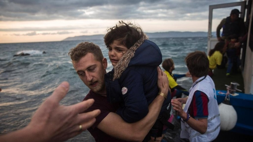A photographer helps a girl to disembark on the Greek island of Lesbos after arriving with around 125 people on a boat from the Turkish coast, Thursday, Oct. 29, 2015. Europe's largest refugee crisis since World War II is entering a perilous and uncharted phase, as the usual pattern of migrant season ending by autumn is overturned by intensifying fighting in Syria and overcrowding in refugee centers in Turkey and Lebanon. (AP Photo/Santo Palacios)