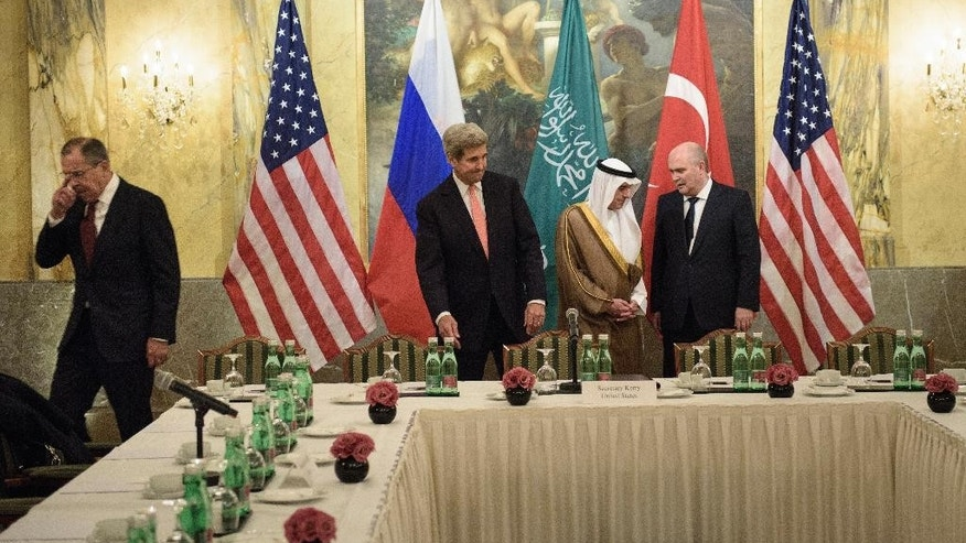 From left, Russian Foreign Minister Sergei Lavrov, Secretary of State John Kerry, Saudi Foreign Minister Adel al-Jubeir and Turkish Foreign Minister Feridun Sinirlioglu take their seats before a meeting in Vienna, Austria, Thursday, Oct. 29, 2015. Kerry and other leaders are in Vienna to discuss solutions to the conflict in Syria. (Brendan Smailowski/Pool via AP)