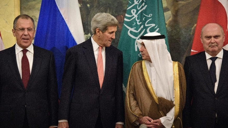 From left, Russian Foreign Minister Sergei Lavrov, Secretary of State John Kerry, Saudi Foreign Minister Adel al-Jubeir and Turkish Foreign Minister Feridun Sinirlioglu stand together before a meeting in Vienna, Austria, Thursday, Oct. 29, 2015. Kerry and other leaders are in Vienna to discuss solutions to the conflict in Syria. (Brendan Smailowski/Pool via AP)