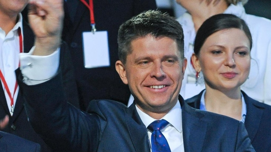 In this Oct. 20, 2015 photo Ryszard Petru greets supporters after a televised parliamentary elections debate in Warsaw, Poland. From radical nationalists and a hardcore rapper to top-level economists, two new parties, one of them led by Petru bring in fresh blood to Poland's parliament following recent election. (AP Photo/Alik Keplicz)