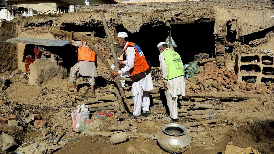 Pakistani volunteers clear the rubble of a house damaged by Monday's earthquake in Kabal near Mingora, Pakistan, Thursday, Oct. 29, 2015. Afghanistan and Pakistan scrambled to rush aid to survivors of this week's magnitude-7.5 earthquake as the region's overall death toll from the temblor rose more than 380. (AP Photo/Naveed Ali)