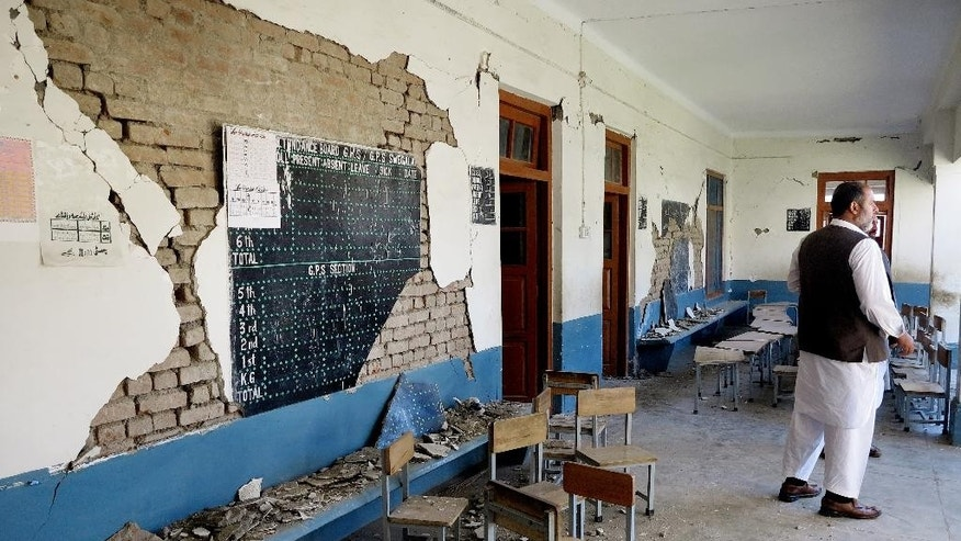 A Pakistani teacher stands in a school damaged by Monday's earthquake in Kabal near Mingora, Pakistan, Thursday, Oct. 29, 2015. Afghanistan and Pakistan scrambled to rush aid to survivors of this week's magnitude-7.5 earthquake as the region's overall death toll from the temblor rose more than 380.  (AP Photo/Naveed Ali)