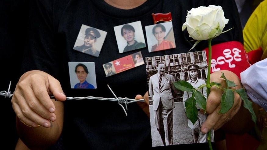 In this July 19, 2015 photo, a woman holds a picture of Gen. Aung San and a white rose at a barricade leading to Martyrs' Mausoleum to pay respect at the tomb of Myanmar's Independence hero and opposition leader Aung San Suu Kyi's father, Gen. Aung San to mark the 68th anniversary of his 1947 assassination. Suu Kyi is the daughter of the country's independence hero, Gen. Aung San, who was assassinated by rivals in 1947, when she was just 2. After many years abroad, she returned in 1988 to Myanmar, previously known as Burma. (AP Photo/Gemunu Amarasinghe)