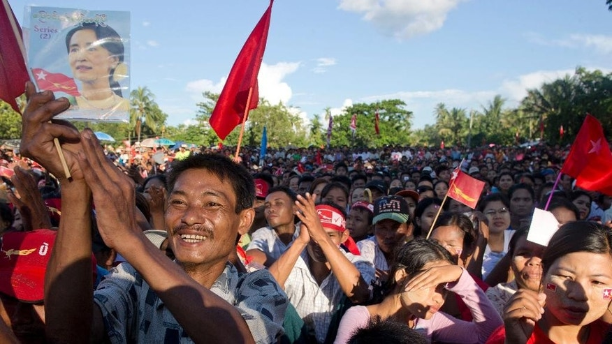 In this Oct 16, 2015 photo, supporters of Myanmar's opposition leader Aung San Suu Kyi applaud as Suu Kyi delivers a speech during a campaign rally of National League for Democracy party in Taungok, western Rakhine state, Myanmar. Suu Kyi's star power has fallen among fellow Myanmar politicians critical of her management style and decision-making, and among fans abroad disenchanted with the Nobel Peace laureate's silence on human-rights abuses. But she's as popular as ever amid the muddy roads and ramshackle huts of her constituency and across much of the country. (AP Photo/Gemunu Amarasinghe)