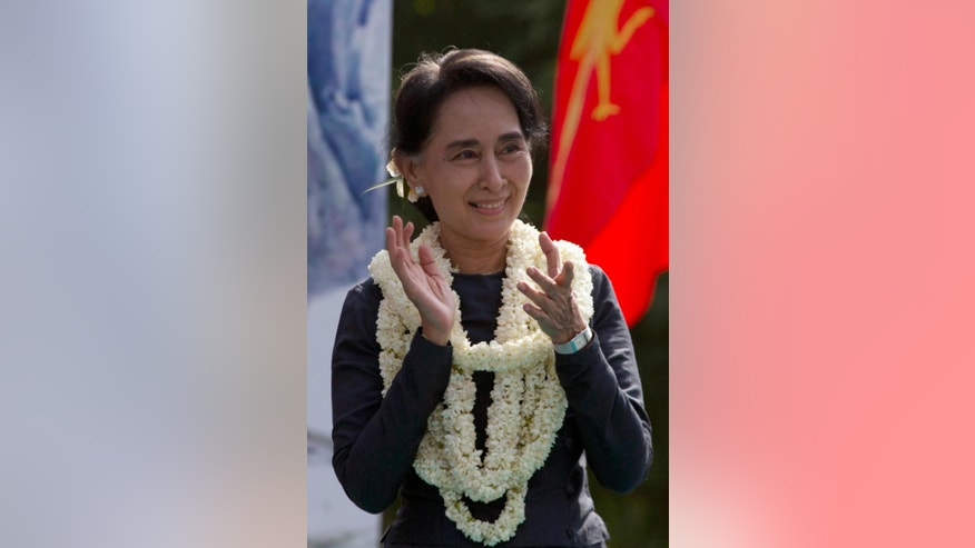 In this Dec.14, 2013 photo, Myanmar's opposition leader Aung San Suu Kyi applauds during a rally in front of thousands of supporters in her constituency Kawhmu township, Yangon, Myanmar. Suu Kyi's star power has fallen among fellow Myanmar politicians critical of her management style and decision-making, and among fans abroad disenchanted with the Nobel Peace laureate's silence on human-rights abuses. But she's as popular as ever amid the muddy roads and ramshackle huts of her constituency and across much of the country. (AP Photo/Gemunu Amarasinghe)