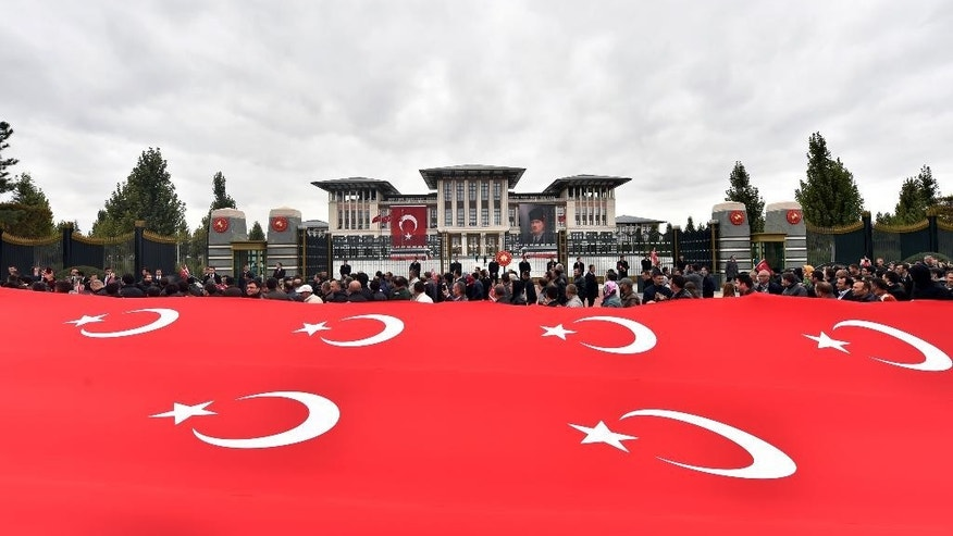 In this Thursday, Oct. 29, 2015 photo made available Friday,Turkish President Recep Tayyip Erdogan, who is barely visible, salutes from a balcony his supporters walking on a main road with national flags outside the gates of his vast presidential palace on Republic Day in Ankara, Turkey. Critics accuse Erdogan of organizing rallies in Turkey and Europe to drum up votes for the ruling Justice and Development Party ahead of Sunday general elections, in breach of laws that require him to be neutral.(AP Photo/Presidential Press Service, Pool )