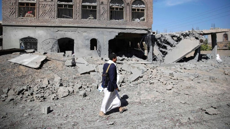 A Shiite fighter, known as a Houthi, walks past of a house damaged by Saudi-led airstrikes in Sanaa, Yemen, Wednesday, Oct. 28, 2015. (AP Photo/Hani Mohammed)