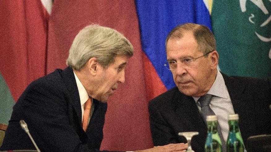 US Secretary of State John Kerry, left, and Russian Foreign Minister Sergey Lavrov share a word prior to the start of the Syria talks at a hotel in Vienna, Austria, Friday, Oct. 30, 2015. Kerry is acknowledging that progress will be difficult as he launches a marathon day of talks aimed at ending the Syrian War but is expressing some hope of headway. With 19 foreign ministers and other senior dignitaries attending, participants say the fact that the talks are happening despite deep divisions among key players are in themselves a sign of success. (Brendan Smialowski/Pool Photo via AP)