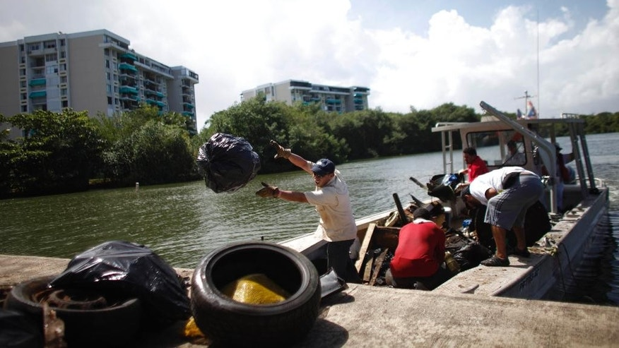 FILE - In this Oct. 26, 2013 file photo, volunteers unload trash they removed from the San Juan Bay Estuary in San Juan, Puerto Rico. In an agreement signed Friday, Oct. 30, 2015, the U.S. has pledged to help clean one of Puerto Rico's most polluted waterways in a move that ends a 15-year struggle to eliminate raw sewage and garbage from a community where thousands of people live. (AP Photo/Ricardo Arduengo, File)