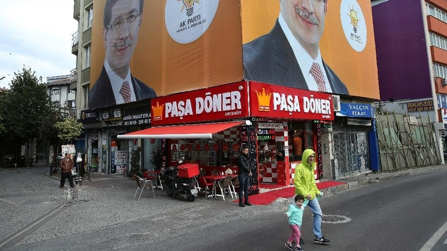A Turkish man with his daughter cross a street as billboard portraits of Turkish Prime Minister and leader of the Justice and Development Party (AKP), Ahmet Davutoglu, covered a building, in Istanbul, Turkey, Saturday, Oct. 31, 2015. Turkish political parties are making their closing appeals ahead of Sunday Nov. 1 crucial parliamentary vote. The election is a redo of June elections in which the ruling Justice and Development Party, or AKP, lost its majority after 13 years of single-party rule.(AP Photo/Hussein Malla)
