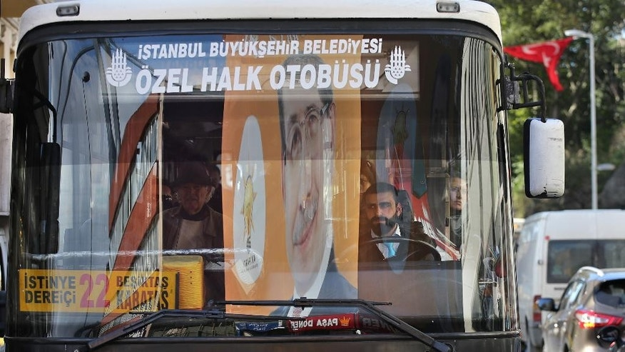 A billboard portrait of Turkish Prime Minister and leader of the Justice and Development Party (AKP), Ahmet Davutoglu, reflected on the front window of a public transport bus, in Istanbul, Turkey, Saturday, Oct. 31, 2015. Turkish political parties are making their closing appeals ahead of Sunday Nov. 1 crucial parliamentary vote. The election is a redo of June elections in which the ruling Justice and Development Party, or AKP, lost its majority after 13 years of single-party rule.(AP Photo/Hussein Malla)