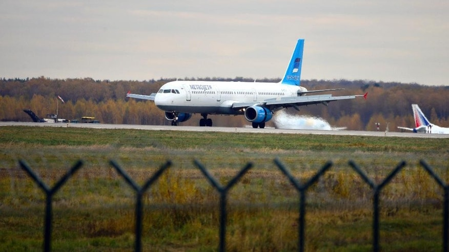 In this photo taken on Tuesday, Oct. 20, 2015, The Russian airline Kogalymavia's Airbus A321 with a tail number of EI-ETJ on an airstrip of Moscow's Domodedovo international airport, outside Moscow, Russia.  Russia's civil air agency is expected to have a news conference shortly to talk about the Russian Metrojet passenger plane EI-ETJ, that Egyptian authorities say has crashed in Egypt's Sinai peninsula. (AP Photo/Tatiana Belyakova)