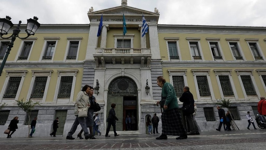 Pedestrians pass outside the headquarters of the National Bank of Greece in Athens, Friday, Oct. 30, 2015. Greece and its bailout creditors remain divided over how to toughen foreclosure laws, according European Union officials, though the overall talks on getting the country the next batch of loans are on track. (AP Photo/Thanassis Stavrakis)