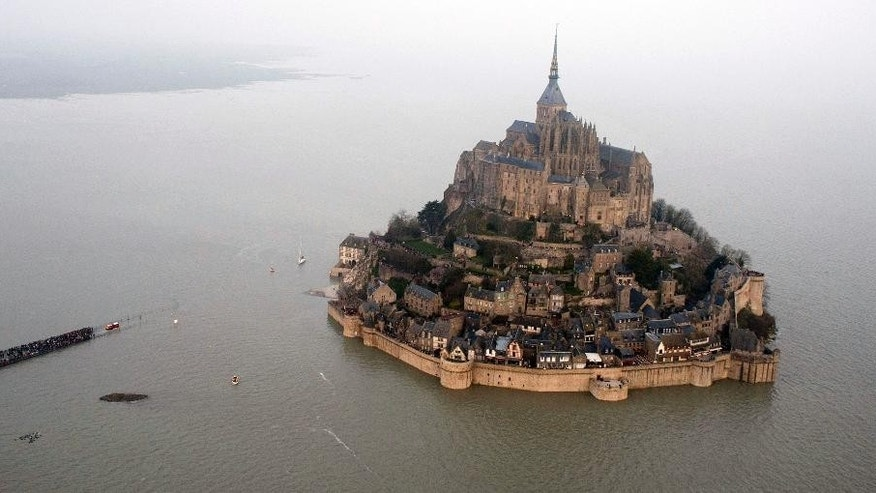 This March 21, 2015 aerial view shows a high tide submergeing a narrow causeway leading to the Mont Saint-Michel, on France's northern coast. French President Francois Hollande is scheduled to visit this unusual Atlantic fortress and tourist site of Mont Saint Michel, an island at high tide and a peninsula at low tide. He's there to finalize construction of a bridge meant to battle erosion and ensure the site's island status. (AP Photo) FRANCE OUT