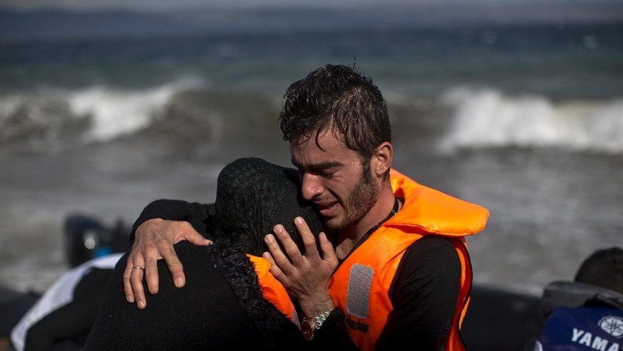A man embraces his wife after they arrived by boat at a beach on the northern coast of Lesbos, Greece, Saturday, Oct. 31, 2015. An official leading rescue efforts on the Greek island of Lesbos has warned that the death toll in the eastern Aegean Sea is likely to rise in the coming days unless urgent action is taken to stop smugglers in nearby Turkey. (AP Photo/Marko Drobnjakovic)