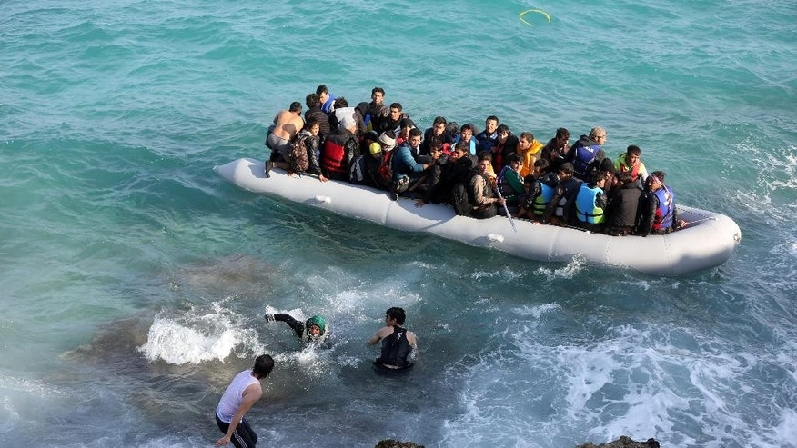 Refugees and migrants board a dingy as they set out, trying to travel from the Turkish coast to the Greek island of Chios, near Cesme, Turkey, Saturday, Oct. 31, 2015. Authorities in Greece say 21 people have died in other islands after two boats carrying migrants and refugees from Turkey to Greece sank overnight, in the latest deadly incidents in the eastern Aegean Sea. (AP Photo/Emre Tazegul)