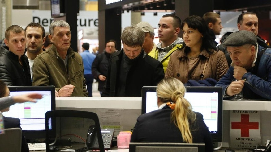 People gather at the airline information desk at of Russian airline Kogalymavia's desk at Pulkovo airport in St.Petersburg, Russia, Saturday, Oct. 31, 2015, after a Russian airliner with 217 passengers and seven crew aboard crashed. Russia's civil air agency is expected to have a news conference shortly to talk about the Russian Metrojet passenger plane that Egyptian authorities say has crashed in Egypt's Sinai peninsula. (AP Photo/Dmitry Lovetsky)