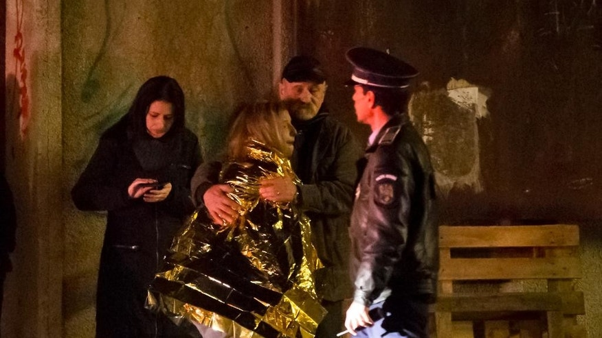 CORRECTS TO REMOVE REFERENCE OF EXPLOSION - A survivor of a fire that occurred in a club in Bucharest, Romania, cries, wrapped in a thermal blanket outside the scene early Saturday, Oct. 31, 2015. A heavy metal band's pyrotechnical show sparked a deadly fire Friday at a Bucharest nightclub, killing more than 20 people and injuring scores of the club's mostly youthful patrons, officials and witnesses said. (AP Photo/Vadim Ghirda)