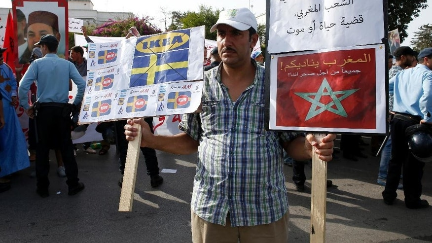 "FILE - In this Oct.4, 2015 file photo, a man holds a placard with Swedish companies and flags with legend in Arabic reading ""The Moroccan Sahara is Moroccan case a matter of life or death"", as some thousands of Moroccans protest outside the Swedish Embassy in Rabat, Morocco. As it marks 40 years since taking control of the mineral-rich Western Sahara, the Moroccan government has been pursuing an especially forceful foreign policy aimed at confronting any challenges to its claims on the territory. And Sweden has become its main target. (AP Photo/Abdeljalil Bounhar, File)"