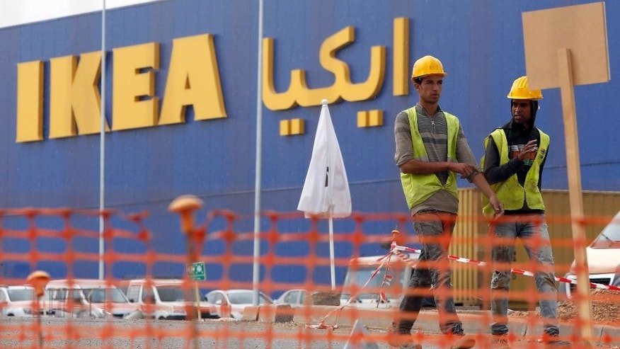 FILE - In this Sept. 29, 2015 file photo, Moroccan workers walk past the construction site of the country's first IKEA store outside Casablanca, Morocco. Morocco is reacting aggressively to any challenges to its claims on Western Sahara, as it marks 40 years since taking control of the mineral-rich territory. Among apparent targets of its wrath: Swedish icons IKEA, Volvo and H&M. This month, the Moroccan government announced it would consider boycotting Swedish products and companies over reports that Sweden was planning to recognize the independence of the Saharawi Arab Democratic Republic, or SADR, which disputes sovereignty over Western Sahara with Morocco. (AP Photo/Abdeljalil Bounhar, File)