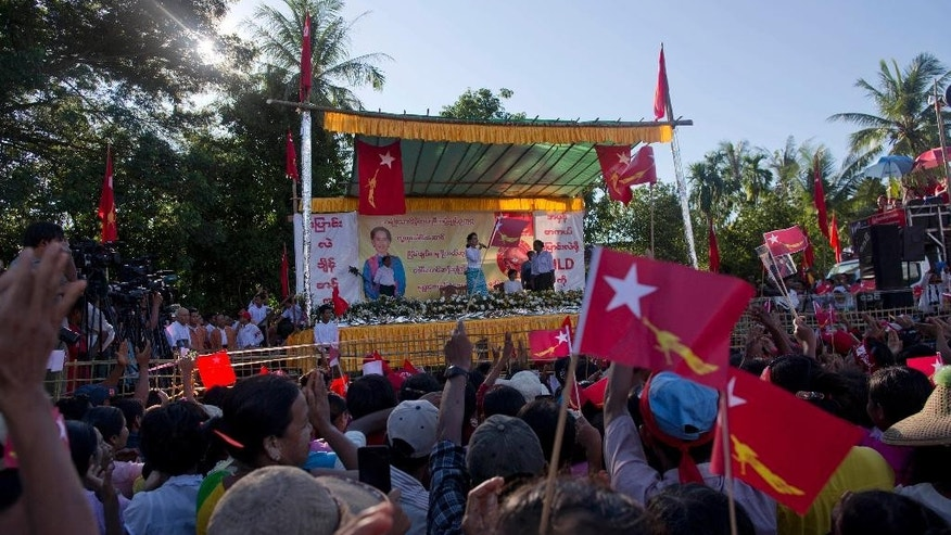 In this Oct. 16, 2015 photo, Myanmar's opposition leader Aung San Suu Kyi, on the stage, delivers a speech as supporters of her National League for Democracy party (NLD) wave party flags and applaud during a campaign rally in Taungok, Western Rakhine state, Myanmar. Suu Kyi, whom the junta kept under house arrest for years, now tours the country stumping for votes. But even if her National League for Democracy wins the Nov. 8 election in a landslide, the odds are that the generals and their cronies will continue to dominate both politics and the economy. (AP Photo/Gemunu Amarasinghe)