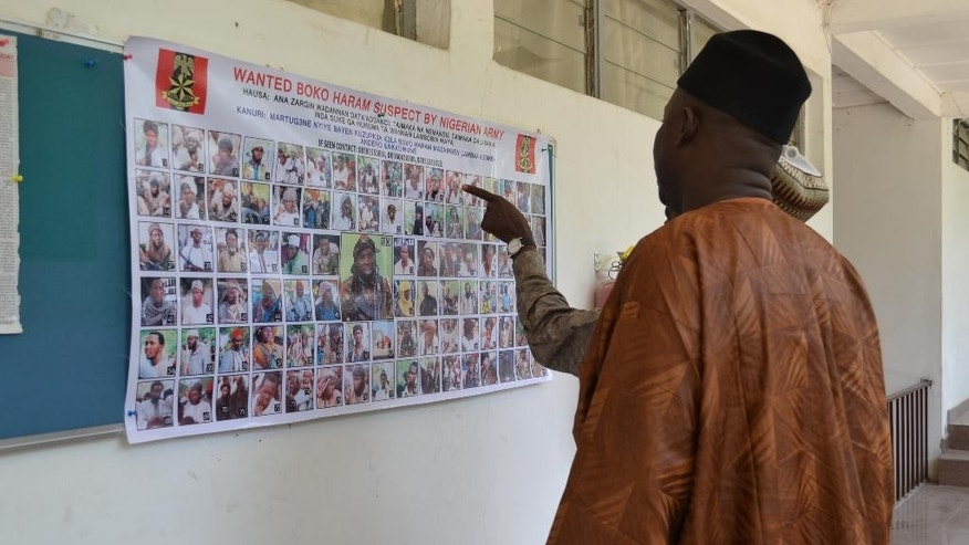 In this photo taken Friday, Oct. 30, 2015, people look at a poster featuring photos of wanted Boko Haram members, pasted onto the wall by Nigeria army in Maiduguri, Nigeria.  Nigeria's army has displayed the poster of 100 photographs of the most wanted Boko Haram militants including the shadowy leader whom they claim to have killed on at least three occasions. (AP Photo/Jossy ola)