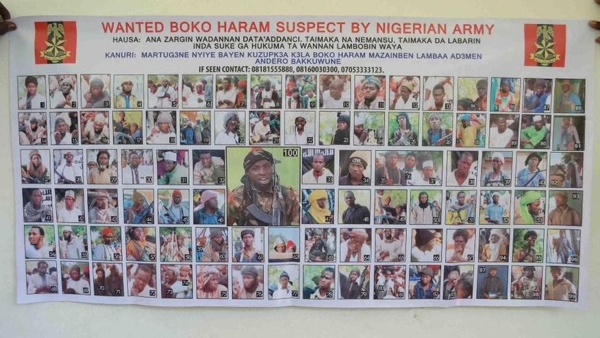 In this photo taken Friday, Oct. 30, 2015,  a poster featuring wanted Boko Haram members, pasted onto the wall by Nigeria army in Maiduguri, Nigeria.  Nigeria's army has displayed the poster of 100 photographs of the most wanted Boko Haram militants including the shadowy leader Abubakar Shekau, large picture at centre, whom they claim to have killed on at least three occasions. (AP Photo/Jossy ola)