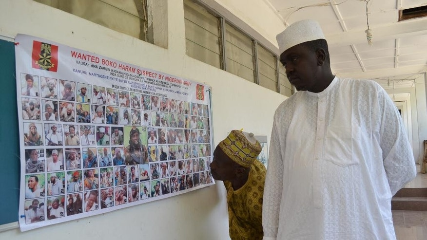 In this photo taken Friday, Oct. 30, 2015, people look at a poster featuring wanted Boko Haram members, pasted onto the wall by Nigeria army in Maiduguri, Nigeria.  Nigeria's army has displayed the poster of 100 photographs of the most wanted Boko Haram militants including the shadowy leader whom they claim to have killed on at least three occasions. (AP Photo/Jossy ola)