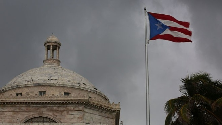 The Puerto Rican flag flies near the Capitol on July 1, 2015 in San Juan, Puerto Rico.