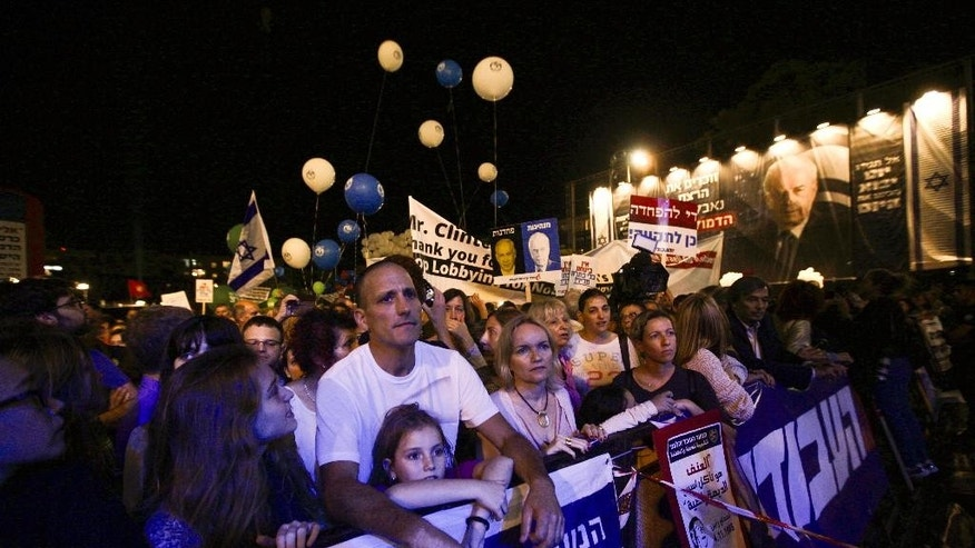 People gather at Rabin Square during a rally marking 20 years since the assassination of the late Israeli Prime Minister Yitzhak Rabin, in Tel Aviv, Israel, Saturday, Oct. 31, 2015. (AP Photo/Sebastian Scheiner)