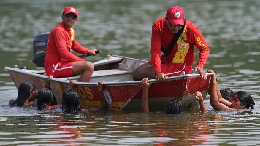 Swimmers hold on to the side of firefighters' boat in the Taguarussu River after they pulled out of the women's swimming event during the World Indigenous Games in Palmas, Brazil, Friday, Oct. 30, 2015. Organizers billed the nine-day-long event as a sort of indigenous Olympics. (AP Photo/Eraldo Peres)