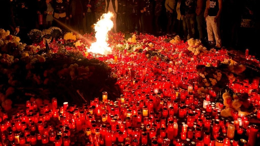 People stand by burning candles outside the compound that housed a nightclub where a fire occurred in the early Saturday in Bucharest, Romania, to pay respects to the victims, marking 24 hours after the accident Sunday, Nov. 1, 2015. Flames spread quickly through the crowded basement club, trapping many and triggering a stampede, making it the deadliest nightclub blaze in Romanian history. (AP Photo/Vadim Ghirda)