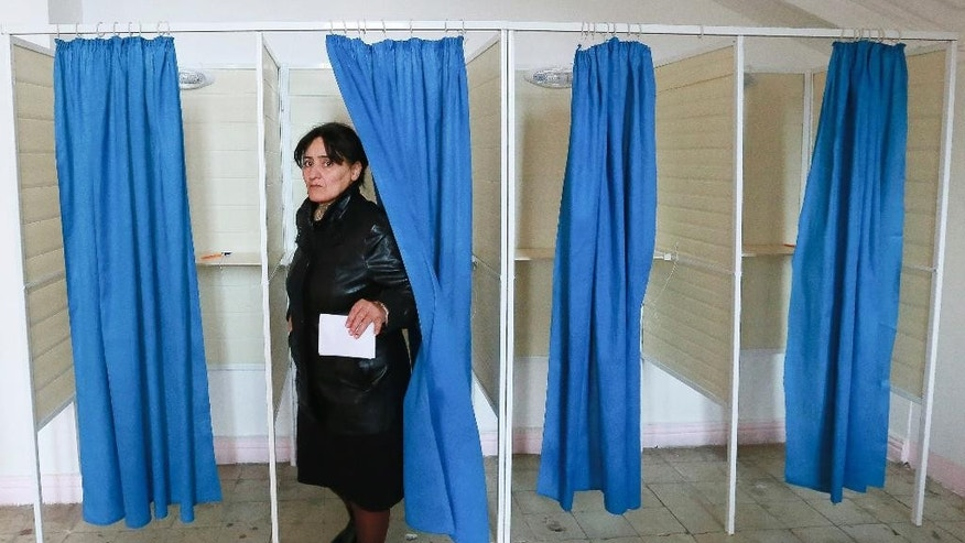 A woman leaves a voting cabin to cast her ballot at a polling station during a parliamentary elections in Baku, Azerbaijan, Sunday, Nov. 1, 2015. Azerbaijani citizens are going to the polls to elect the 125 members of parliament. Voters in the oil-rich Caspian Sea nation of Azerbaijan are casting ballots in a parliamentary election expected to secure the ruling party's dominance. (AP Photo/Aziz Karimov)