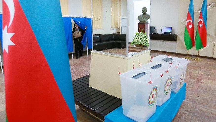 A woman leaves a voting cabin to cast her ballot at a polling station decorated with the national flag during a parliamentary elections in Baku, Azerbaijan, Sunday, Nov. 1, 2015. Voters in the oil-rich Caspian Sea nation of Azerbaijan cast ballots Sunday in a parliamentary election that is expected to secure the ruling party's dominance. (AP Photo/Aziz Karimov)
