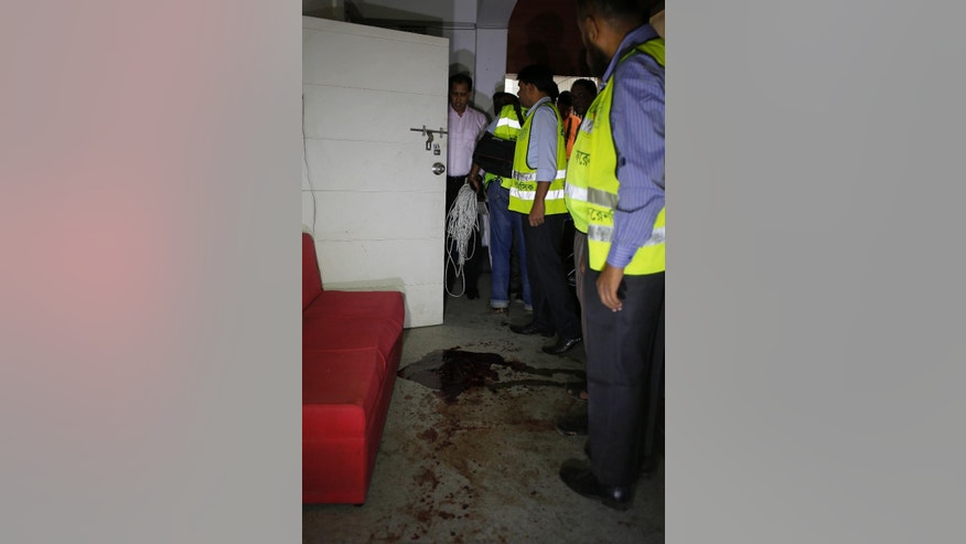 Bangladeshi security officers inspect the blood-stained site where publisher Ahmed Rahim Tutul and two writers were shot and stabbed by three men in the office of the Shudhdhoswar publishing house, in Dhaka, Bangladesh, Saturday, Oct. 31, 2015. A publisher of secular books was hacked to death in a separate attack Saturday at another publishing house in Bangladesh's capital, police said. The attacks in Dhaka come amid fears about the rise of radical Islam in Bangladesh. (AP Photo/A.M. Ahad)