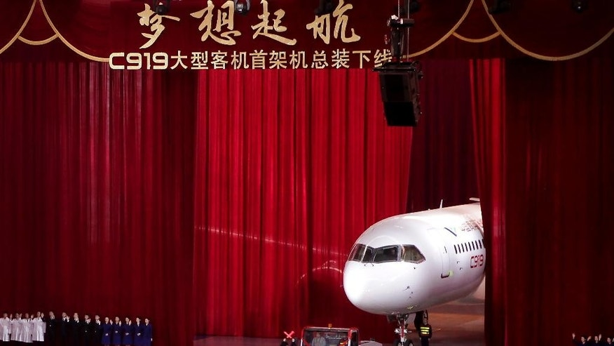 Chinese workers wave as a truck pulls out the first twin-engine 158-seater C919 passenger plane made by The Commercial Aircraft Corp. of China (COMAC) during a ceremony at the company's hangar near the Pudong International Airport in Shanghai, China, Monday, Nov. 2, 2015. The first plane produced by a Chinese government initiative to compete in the market for large passenger jetliners has been unveiled in Shanghai. (AP Photo)