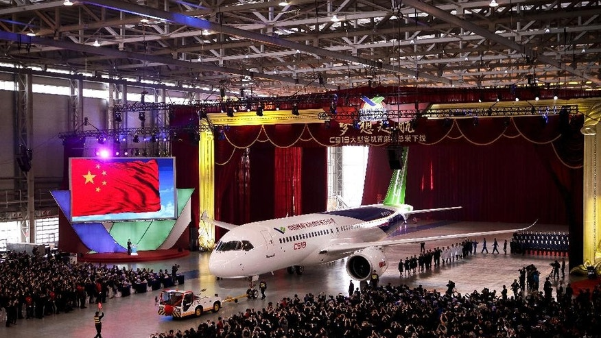 The first twin-engine 158-seater C919 passenger plane made by The Commercial Aircraft Corp. of China (COMAC) is pulled out of the company's hangar during a ceremony near the Pudong International Airport in Shanghai, China, Monday, Nov. 2, 2015. The first plane produced by a Chinese government initiative to compete in the market for large passenger jetliners has been unveiled in Shanghai. (AP Photo)