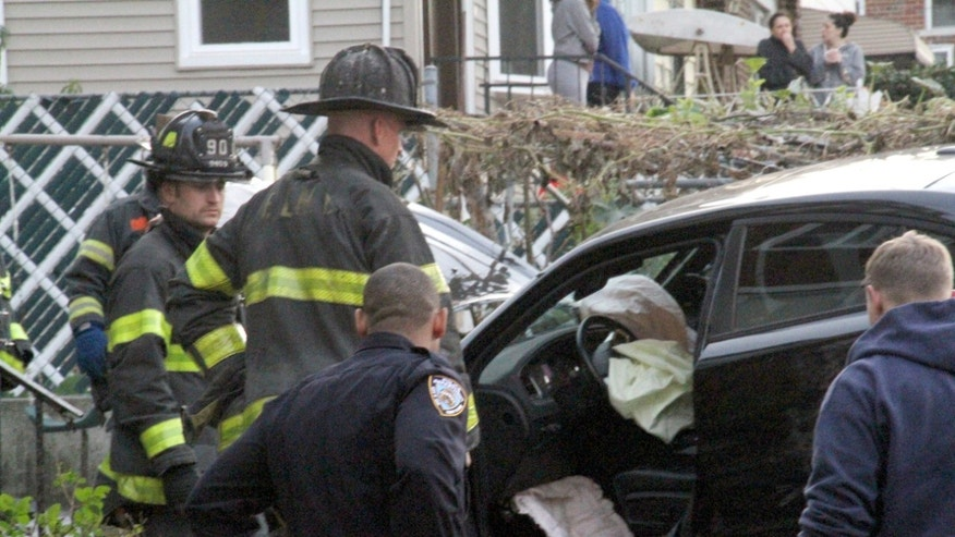 First responders examine a car after driver lost control and plowed into group of trick-or-treaters in New York, Oct. 31, 2015.